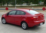 A three-quarter rear view of a red 2012 Kia Rio EX