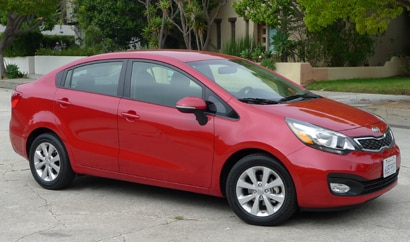 A three-quarter front view of a red 2012 Kia Rio EX
