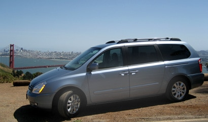 A side view of a light blue 2008 Kia Sedona EX, with San Francisco's Golden Gate Bridge in the background