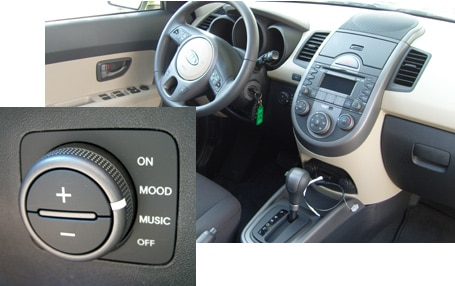 An interior view of a 2010 Kia Soul with an overlapped shot of the light-up speaker control