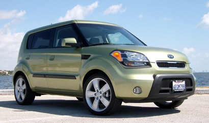 A three-quarter front view of a light green 2010 Kia Soul in Miami Beach, Florida