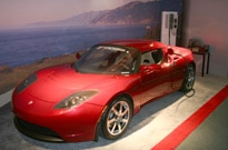 A three-quarter front view of a red Tesla Roadster