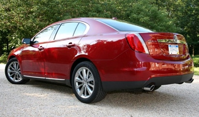 A three-quarter rear view of a red 2009 Lincoln MKS