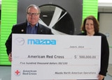 Jim O'Sullivan, CEO of Mazda North America, presents a check to the American Red Cross