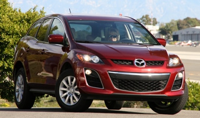 A three-quarter front view of a Copper Red 2010 Mazda CX-7 i Sport FWD