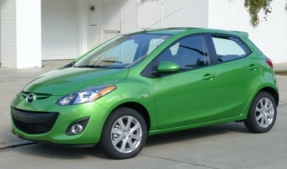 A three-quarter front view of a green Mazda 2