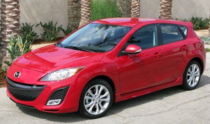 A three-quarter front view of a red 2010 Mazda 3 s