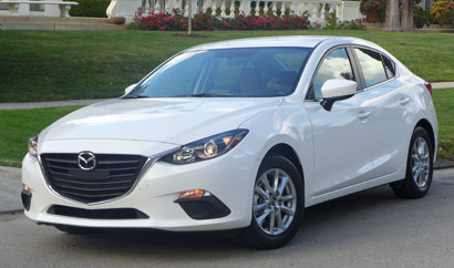 A three-quarter front view of the Mazda 3 i 4-Door Touring