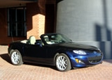 A three-quarter front view of a dark blue 2009 Mazda MX-5 Miata