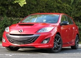 A three-quarter front view of a red 2013 Mazdaspeed3 Touring