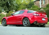 A three-quarter rear view of a red 2009 Mazda RX-8 R3