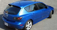 A three-quarter rear view of a blue 2004 Mazda 3