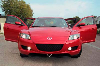 A front view of a red 2004 Mazda RX-8 with all of its four doors open