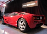 A three-quarter rear view of a red McLaren F1
