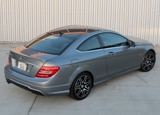 A three-quarter rear view of a silver 2013 Mercedes-Benz C250 Coupe