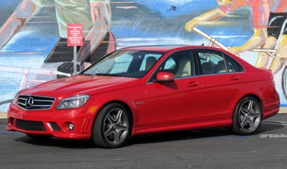 A three-quarter front view of a red 2010 Mercedes-Benz C63