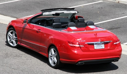 A three-quarter rear view of a red Mercedes-Benz E550 Cabriolet