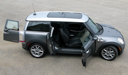 A side view of a gray and white 2008 Mini Cooper S Clubman with its doors open