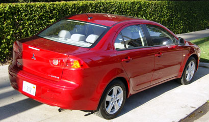 A three-quarter rear view of a red 2008 Mitsubishi Lancer ES