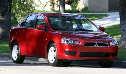 A three-quarter front view of a red 2008 Mitsubishi Lancer ES