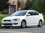 A three-quarter front view of a white 2010 Mitsubishi Lancer ES