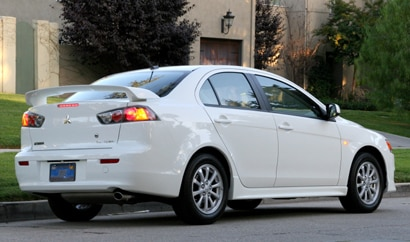 A three-quarter rear view of a white 2010 Mitsubishi Lancer ES