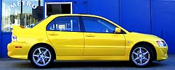 A side view of a yellow Mitsubishi Lancer Evolution VIII