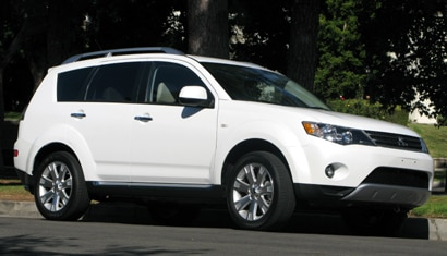 A three-quarter front view of a white 2009 Mitsubishi Outlander SE