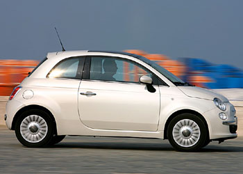 A side view of a speeding white 2007 Fiat 500
