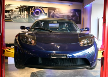 A front view of a dark blue 2008 Tesla Roadster on display at Tesla Motor's Los Angeles dealership