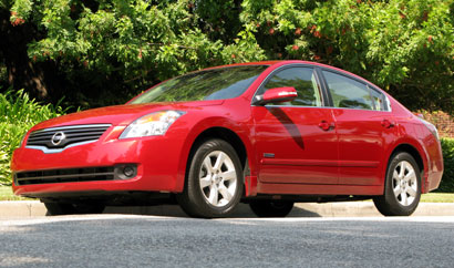 A three-quarter front view of a red Nissan Altima Hybrid