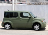 A side view of a green 2010 Nissan Cube