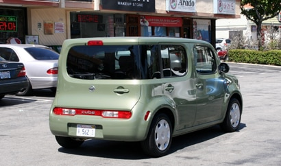 A three-quarter rear view of a green 2010 Nissan Cube 1.8 S