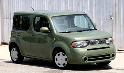 A three-quarter front view of a green 2010 Nissan Cube 1.8 S