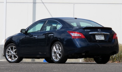 A three-quarter rear view of a navy blue 2010 Nissan Maxima 3.5 SV Sport