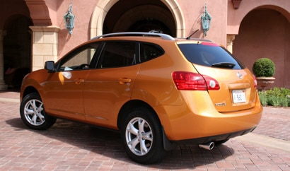 A three-quarter rear view of an orange 2008 Nissan Rogue SL 2WD