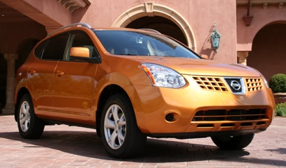 A three-quarter front view of an orange 2008 Nissan Rogue SL 2WD