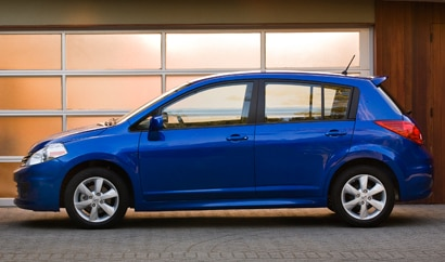 A side view of a blue 2011 Nissan Versa 5-door hatchback