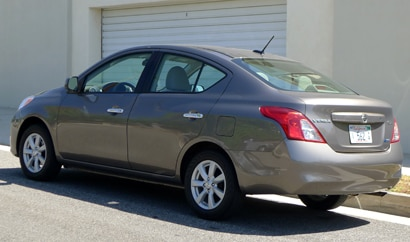 A three-quarter rear view of a 2012 Nissan Versa 1.6 SL Sedan