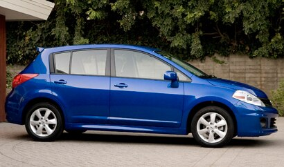 A side view of a blue 2012 Nissan Versa Hatchback
