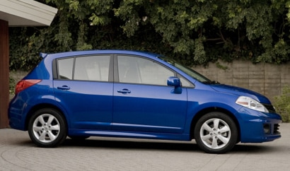 A side view of a blue 2012 Nissan Versa Hatchback