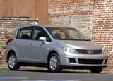 A three-quarter front view of a silver 2009 Nissan Versa SL