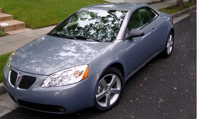 A three-quarter front view of a Pontiac G6 GT Convertible with its hardtop up