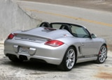 A three-quarter rear view of a silver 2011 Porsche Boxster Spyder