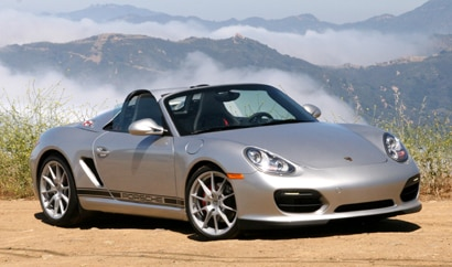 A three-quarter front view of a silver 2011 Porsche Boxster Spyder
