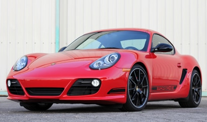 A three-quarter front view of a red 2012 Porsche Cayman R