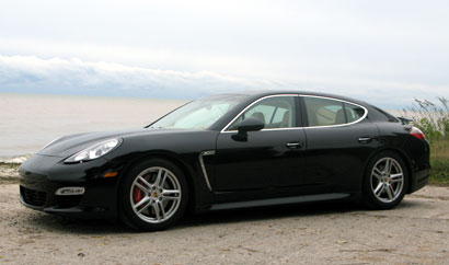 A three-quarter front view of a black 2010 Porsche Panamera Turbo on a beach