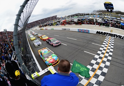 The green flag waves at the 2014 NASCAR Sprint Cup Series STP 500 at Martinsville Speedway