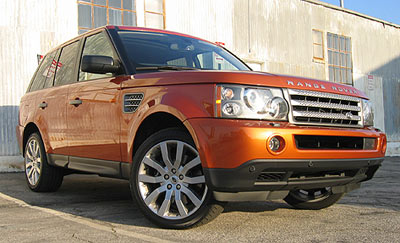 A three-quarter front view of an orange 2006 Range Rover Sport Supercharged