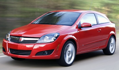 A three-quarter front view of a red 2008 Saturn Astra XR in motion
